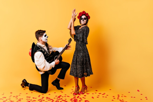 Full-length shot of extraordinary creative couple dancing and singing on orange wall. girl and boy with skull masks posing