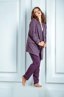 Full length shot, of fashion model in oversize violet suit. studio shot