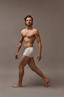 Full length shot of fit attractive tattooed man with muscular perfect body walking isolated wearing white boxer shorts. handsome bearded guy demonstrating his muscles, having confident look