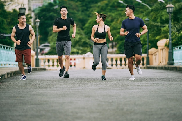 Full-length shot of four people jogging in the morning
