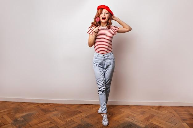 Colpo integrale della ragazza francese in jeans alla moda che mangia lecca-lecca. foto interna di attraente donna allo zenzero con caramelle.