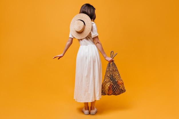 Colpo integrale di ragazza in abito midi con cappello di paglia e borsa di stringa con frutta su sfondo arancione.