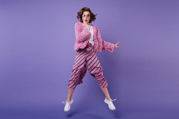 Colpo integrale di donna riccia felice in pantaloni a righe che salta sulla parete viola. ritratto dell'interno della ragazza meravigliosa in occhiali da sole che scherza.