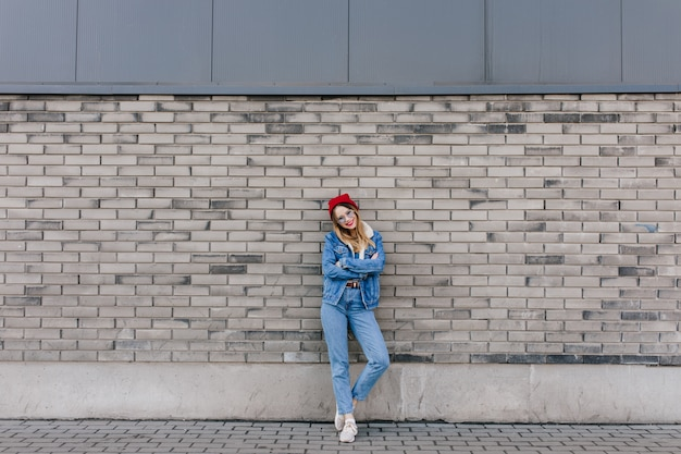 Full-length shot of gorgeous woman in white sneakers posing on urban wall with arms crossed. outdoor portrait of attractive female model in red hat standing in front of brick wall.