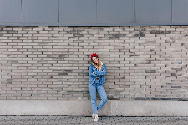 Colpo integrale di splendida donna in scarpe da ginnastica bianche in posa sul muro urbano con le braccia incrociate. ritratto all'aperto del modello femminile attraente in cappello rosso che sta davanti al muro di mattoni.