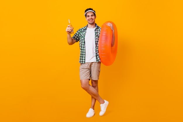 Full-length shot of guy in beige shorts, t-shirt and plaid shirt posing with bottle of beer and rubber ring.