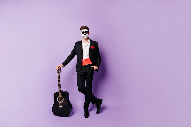Full-length shot of guy posing relaxed with guitar. man with painted face in spanish-style suit looks into camera.