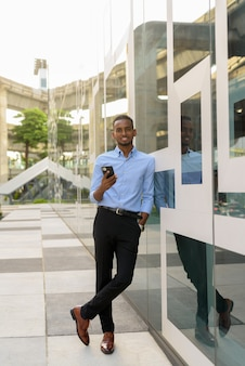 Full length shot of handsome black african businessman outdoors in city during summer smiling and holding mobile phone vertical shot
