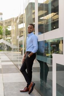 Full length shot of handsome black african businessman outdoors in city during summer vertical shot