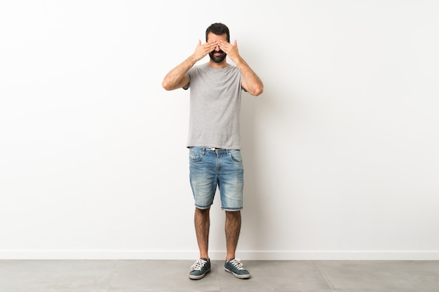 A full-length shot of handsome man with beard covering eyes by hands