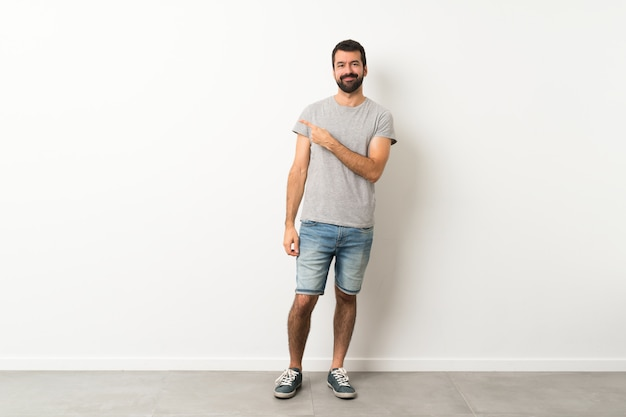 A full length shot of handsome man with beard pointing to the side to present a product