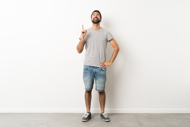 A full length shot of handsome man with beard pointing up and surprised