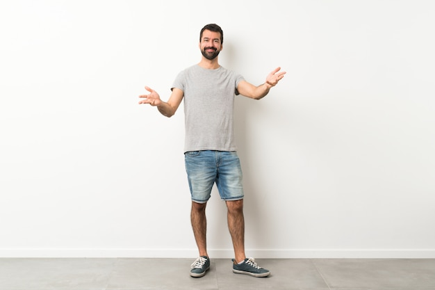 A full length shot of handsome man with beard presenting and inviting to come with hand