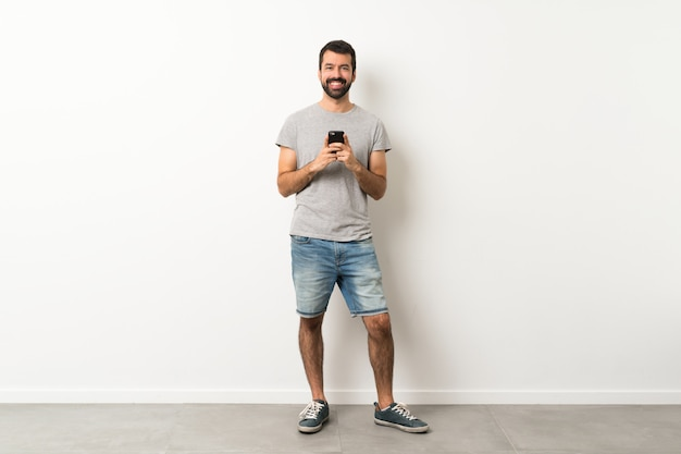A full length shot of handsome man with beard sending a message with the mobile