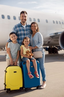 Full length shot of happy family of four standing in front of big airplane on a daytime and smiling at camera. people, traveling, vacation concept