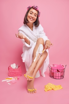 Full length shot of happy young asian lady mkaes hairstyle shaves legs and does pedicure dressed in white bathrobe poses on toilet bowl against pink wall basket with toilet paper roller
