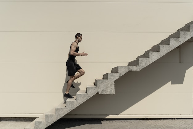 Full length shot of healthy athletic man climbing up on stairs.