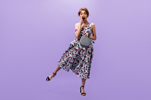 Full length shot of lady holding bag and shouting. attractive cool woman in floral bright outfit jumpin on isolated background.