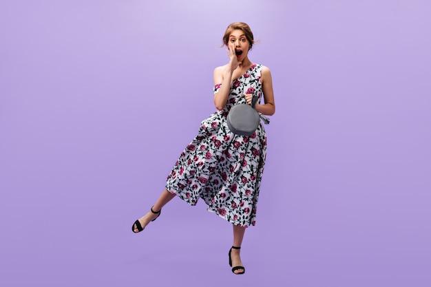Colpo integrale della signora che tiene la borsa e che grida. attraente donna fresca in abito luminoso floreale jumpin su sfondo isolato.