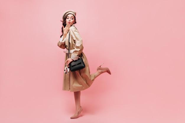 Colpo a figura intera della signora in trench midi che solleva civettuolo la gamba e soffia un bacio su sfondo rosa.