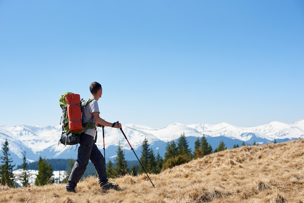 Full length shot of a male backpacker with a backpack hiking in the mountains
