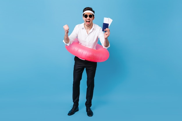 Full-length shot of man enjoying vacation trip. guy in business suit and sunglasses holding documents, tickets and pink inflatable circle.