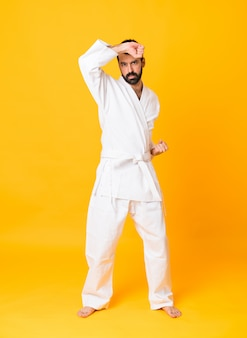 Full-length shot of man over isolated yellow doing karate