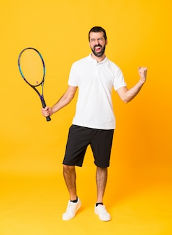 Full-length shot of man over isolated yellow wall playing tennis and celebrating a victory