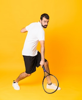 Full-length shot of man playing tennis over isolated yellow
