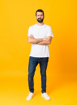 Full-length shot of man with beard over isolated yellow background feeling upset