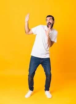 Full-length shot of man with beard over isolated yellow background nervous and scared