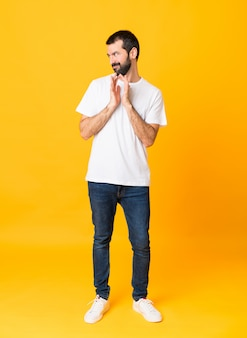 Full-length shot of man with beard over isolated yellow background scheming something
