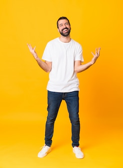 Full-length shot of man with beard over isolated yellow background smiling a lot