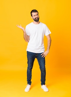 Full-length shot of man with beard over isolated yellow background unhappy for not understand something