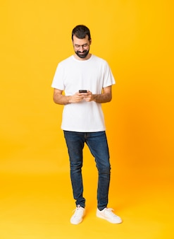 Full-length shot of man with beard over isolated yellow sending a message with the mobile