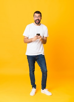 Full-length shot of man with beard over isolated yellow surprised and sending a message