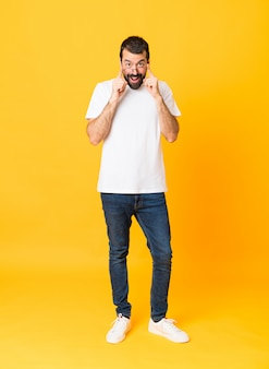 Full-length shot of man with beard over isolated yellow with glasses and surprised