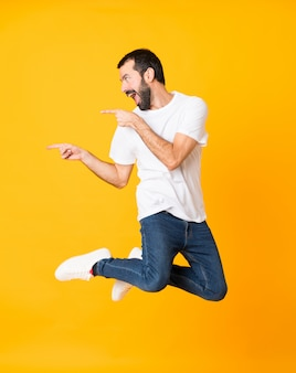 Full-length shot of man with beard jumping and pointing to the lateral over isolated yellow
