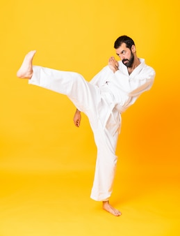 Full-length shot of mandoing karate over isolated yellow