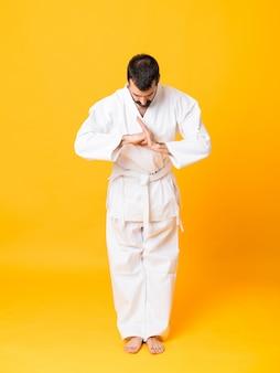 Full-length shot of mandoing karate over isolated yellow