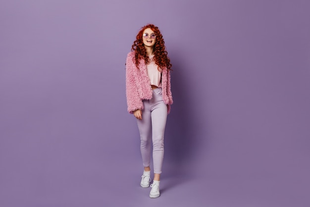 Full-length shot of naughty red-haired girl in round glasses, white jeans and pink coat on purple space.