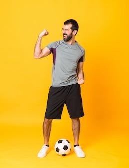 Полнометражный снимок футболиста над изолированным желтым