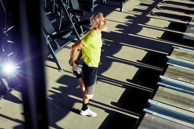 워밍업 스트레칭 운동을하는 운동복에 성숙한 운동 남자의 전체 길이 샷