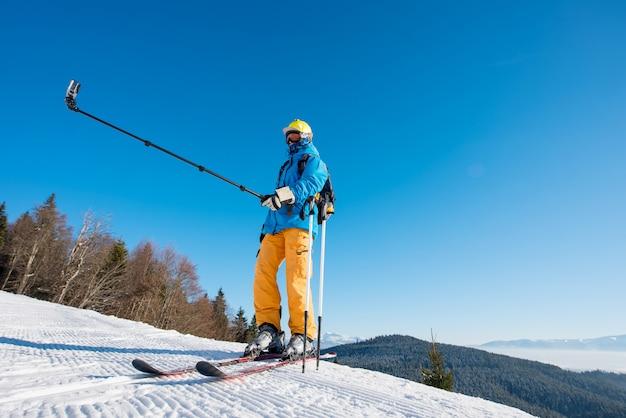 Полная длина выстрел лыжника, стоящего на вершине горы в солнечный зимний день, принимая селфи