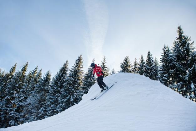 山でスキーをする女性の全身ショット