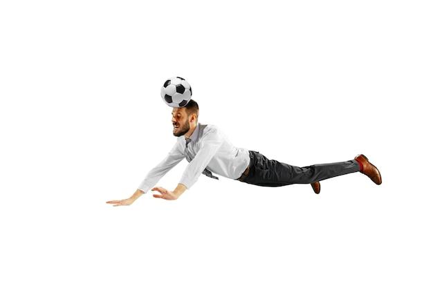 白い背景で隔離のサッカーをしている青年実業家のフルレングスのショット。