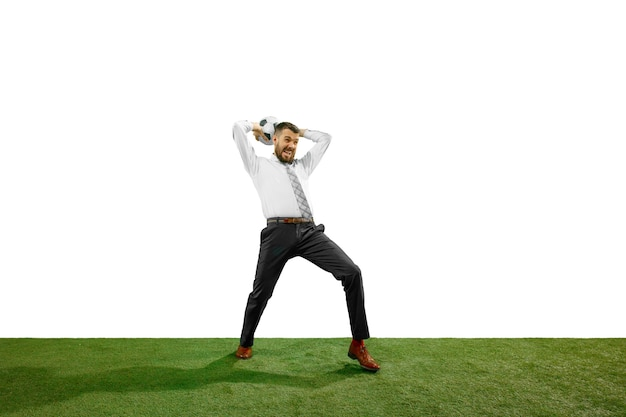 흰 벽에 고립 된 축구를하는 젊은 사업가의 전체 길이 샷