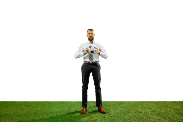 Полнометражный снимок молодого бизнесмена, играющего в футбол, изолированного на белой стене