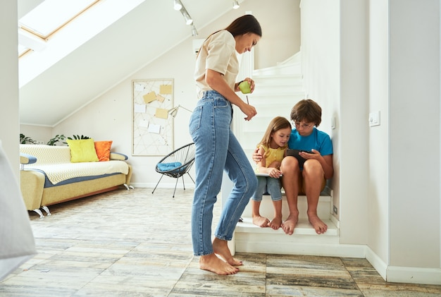 Снимок в полный рост молодой матери, помогающей детям с домашним заданием дома, где сидят брат и сестра
