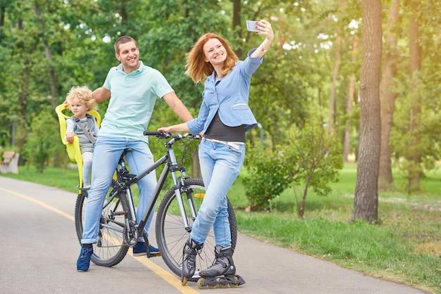 공원 카피스페이스에서 스마트 폰으로 셀카를 찍는 자전거를 타고 남편과 아기와 함께 포즈를 취한 롤러블레이드를 입은 젊은 여성의 전체 길이 사진.